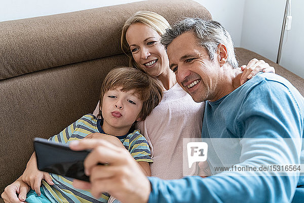 Father  mother and son taking a selfie on couch at home