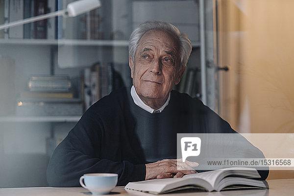 Älterer Mann liest zu Hause Buch