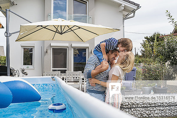 Father with wife carrying son on shoulders in garden