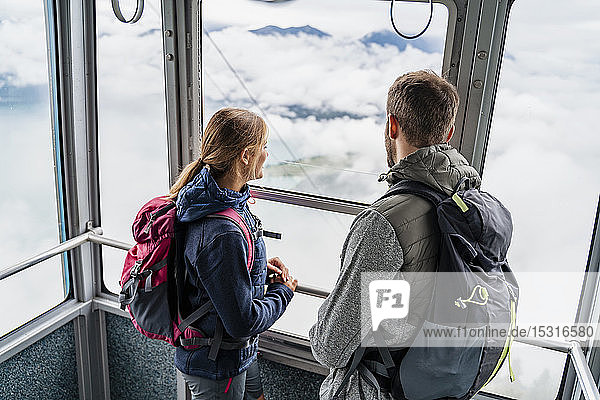 Young couple in a gondola cableway looking out of window  Herzogstand  Bavaria  Germany
