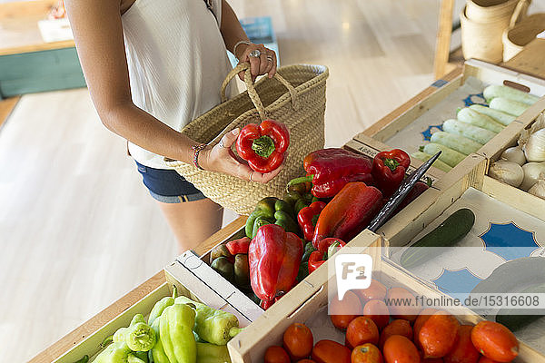 Junge Frau im Bioladen wählt Gemüse aus Junge Frau im Bioladen wählt Gemüse aus