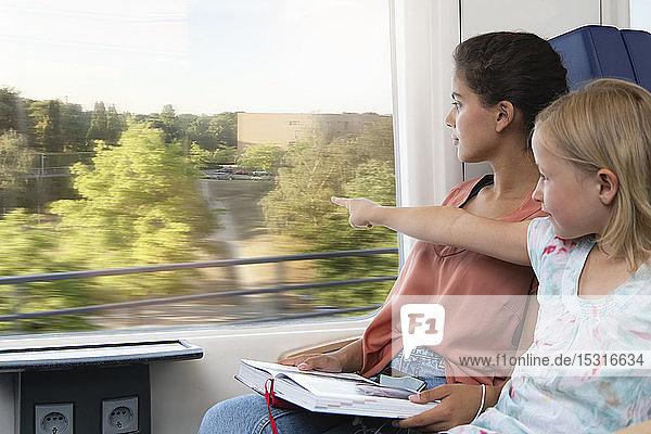 Zwei Schwestern sitzen in einem Zug und lesen ein Buch