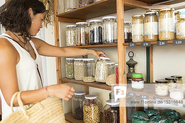 Junge Frau im Bioladen schaut sich Getreide in Gläsern an
