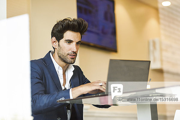 Focused businessman using laptop in an urban cafe