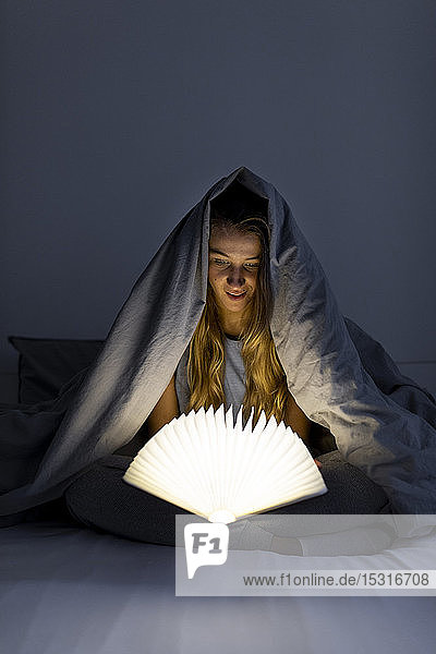 Young woman reading illuminated book in bed at home