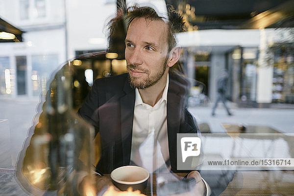 Porträt eines Geschäftsmannes in einem Café  der aus dem Fenster schaut