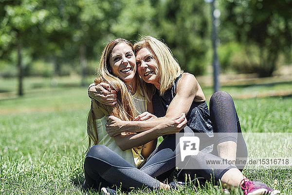 Sportliche reife Frau und ihre Tochter umarmen sich auf einer Wiese in einem Park