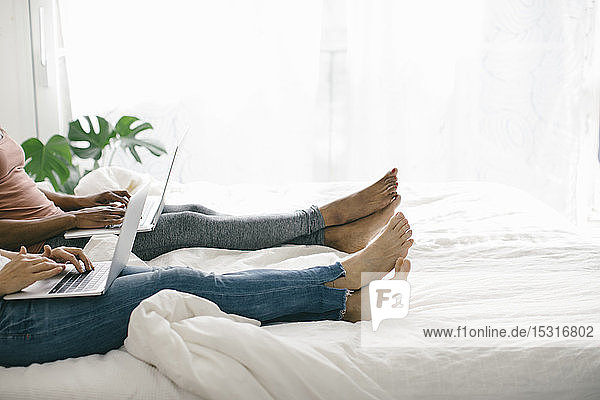 Legs of two women lying in bed at home using laptops