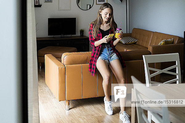 Happy young woman with cell phone and healthy drink at home