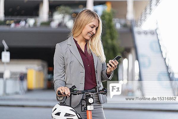 Lächelnde Geschäftsfrau mit Elektroroller schaut auf Handy