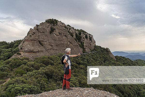 Wanderer zeigt mit Wanderstock,  auf Aussichtspunkt stehend