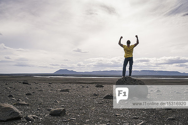 Erwachsener Mann steht mit erhobenen Armen auf einem Felsen im vulkanischen Hochland von Island