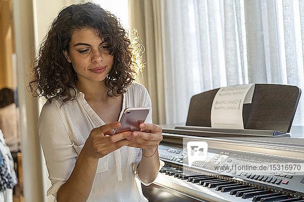 Junge Frau  die zu Hause am Klavier mobil telefoniert