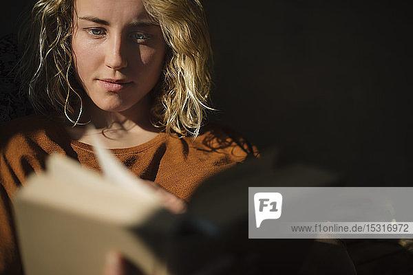 Blonde junge Frau liest ein Buch