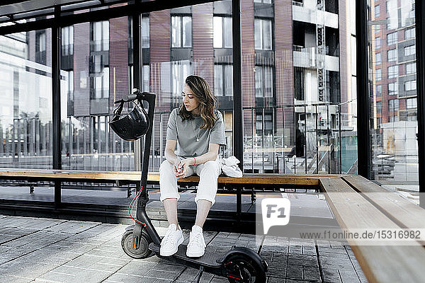 Woman with e-scooter sitting on a bench
