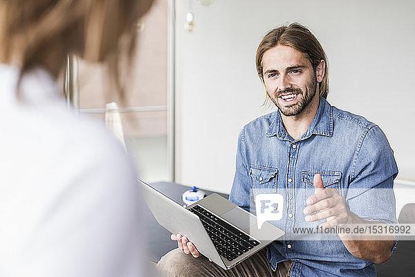 Junger Geschäftsmann mit Laptop im Gespräch mit einer Geschäftsfrau im Büro