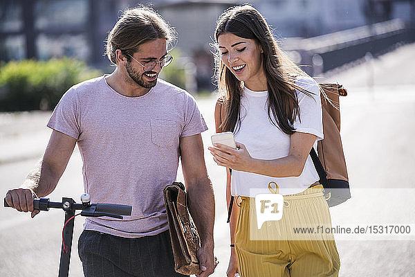 Junges Paar mit Elektroroller und Smartphone auf der Straße