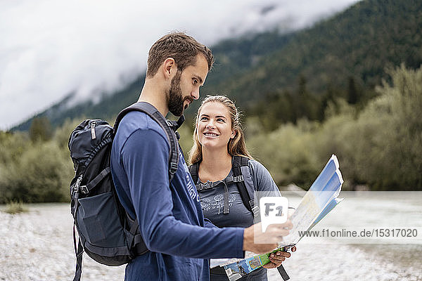 Young couple on a hiking trip reading map  Vorderriss  Bavaria  Germany