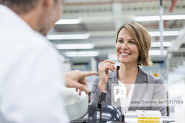 Smiling businesswoman and man talking at assembly robot in a factory