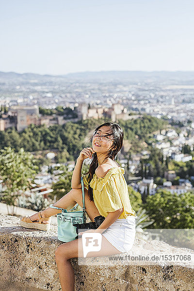 Smiling young woman with camera sitting on a wall at the Alhambra,  Granada,  Spain