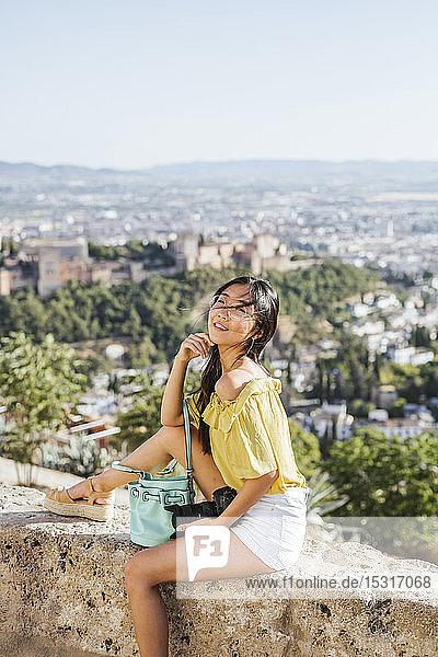 Lächelnde junge Frau mit Kamera an einer Wand in der Alhambra  Granada  Spanien