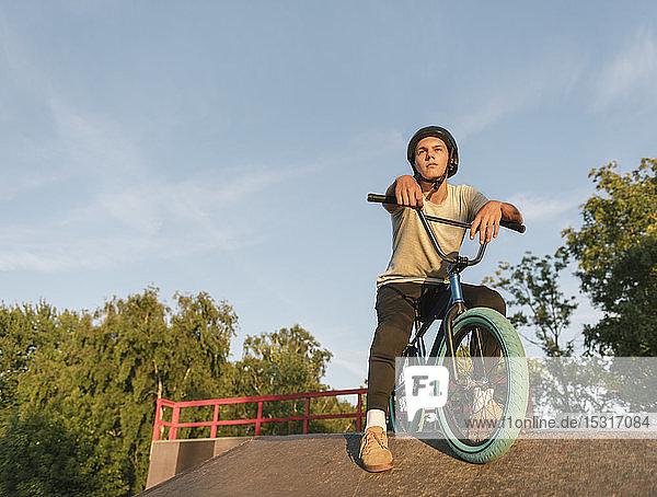 Junger Mann mit BMX-Rad im Skatepark bei einer Pause