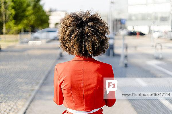 Rückenansicht einer jungen Frau mit modischer roter Anzugsjacke
