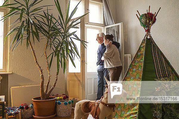 Älteres Ehepaar steht im Kinderzimmer und schaut aus dem Fenster