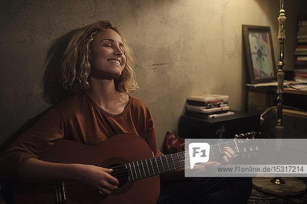 Glückliche junge Frau spielt zu Hause Gitarre