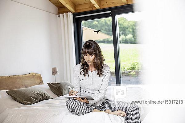 Frau benutzt Tablette am Bett zu Hause