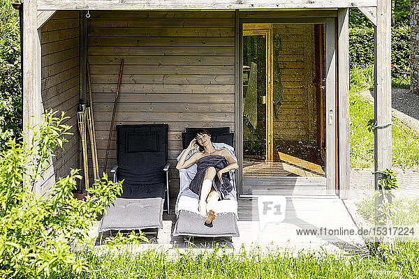 Woman relaxing on a lounge outside sauna