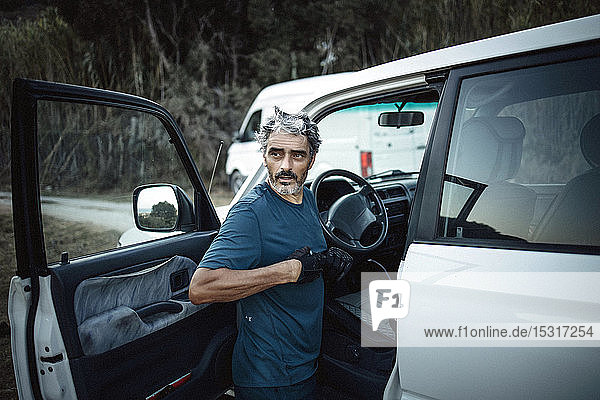 Mature man standing at his off-road vehicle