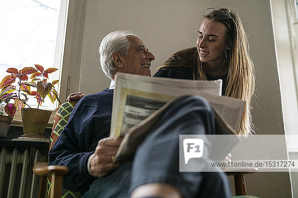 Happy young woman and senior man with newspaper at home
