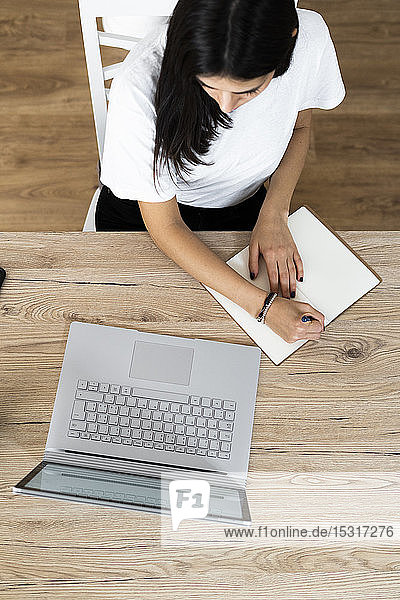 Top view of young woman with laptop taking notes