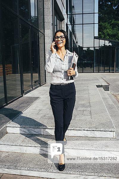 Lächelnde junge Geschäftsfrau telefoniert vor dem Bürogebäude