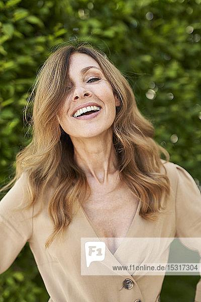 Porträt einer lachenden  reifen Frau  Hecke im Hintergrund