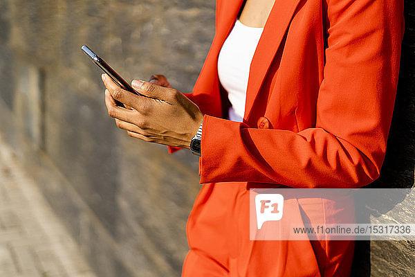 Frau in modischem roten Hosenanzug mit Handy in der Hand  Teilansicht
