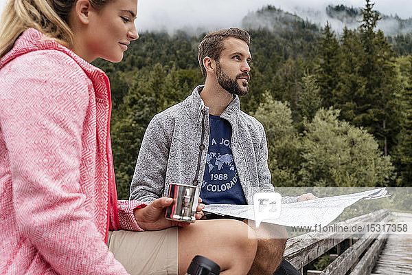 Young couple on a hiking trip with drink and map  Vorderriss  Bavaria  Germany