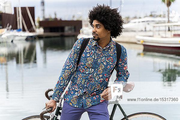 Stilvoller Mann mit Fahrrad am Yachthafen