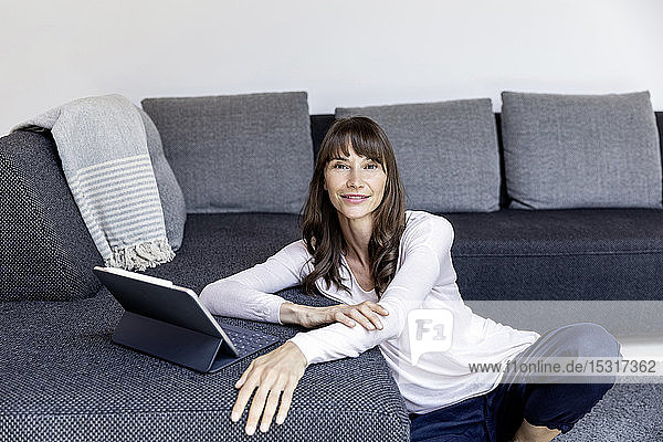 Portrait of smiling woman using tablet in living room at home