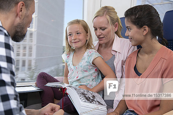 Familie reist mit dem Zug  Töchter lesen ein Buch