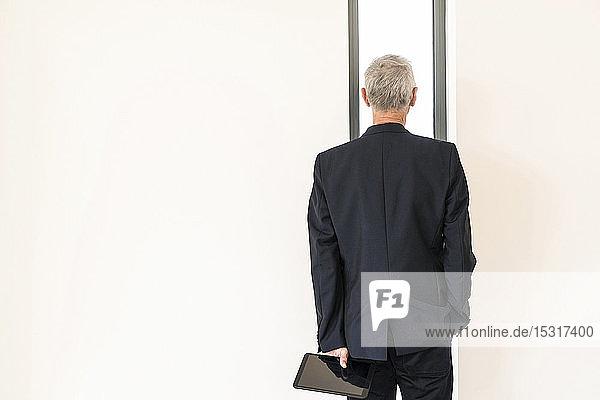 Rückansicht eines leitenden Geschäftsmannes mit Tablette  der durch ein Fenster schaut