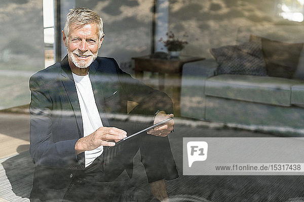Smiling senior businessman using tablet at the window