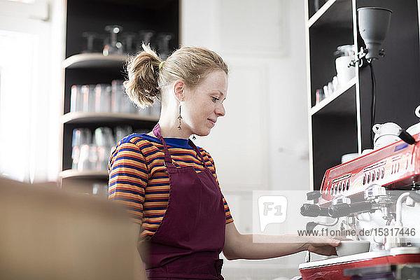 Frau mit Schürze bei der Arbeit in einem Cafe