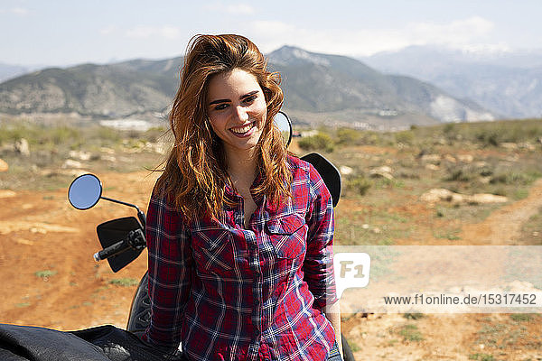 Portrait of happy redheaded woman with motorbike in nature  Andalusia  Spain