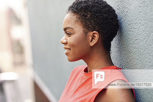 Profile of smiling young woman leaning against wall