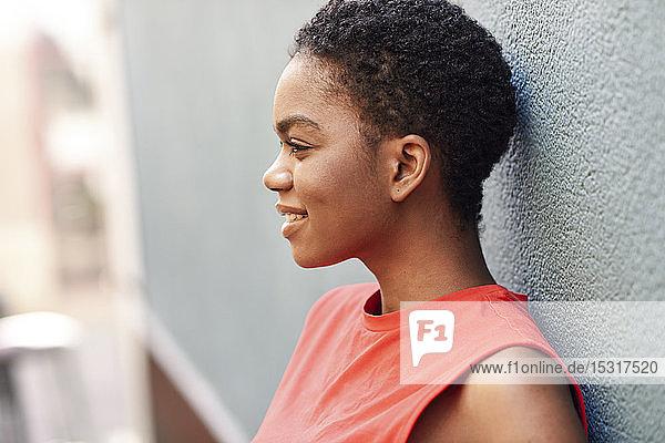 Profil einer lächelnden jungen Frau  die an einer Wand lehnt