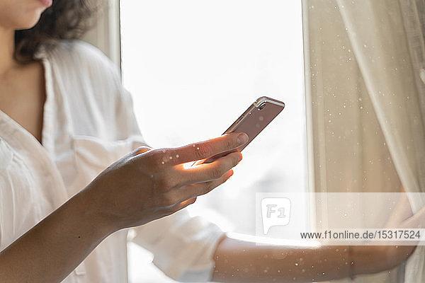Nahaufnahme einer Frau  die zu Hause am Fenster ein Mobiltelefon benutzt