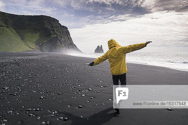 Ein erwachsener Mann geht mit ausgestreckten Armen an einem Lavastrand in Island