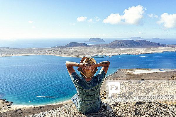 Mann auf Aussichtspunkt mit Blick auf die Insel La Gracioas von Lanzarote  Kanarische Inseln  Spanien